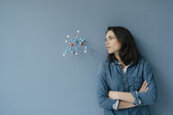 Female scientist studying molecule model, looking for solutions - KNSF05648