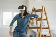 Woman with VR glasses, leaning on ladder - KNSF05654