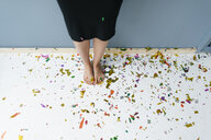 Woman standing on confetti with bare feet - KNSF05660