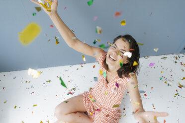 Happy woman sitting on ground, throwing confetti - KNSF05666
