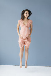 Woman pretending to be pregnant, jumping for joy - KNSF05681