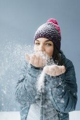 Woman wearing wooly hat, blowing snow - KNSF05684