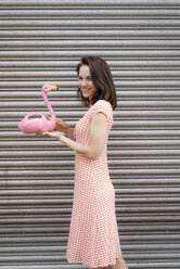 Woman in summer dress with heart pattern, holding pink flamingo figure - KNSF05696