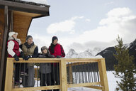 Family on lodge deck below snowy mountains - HEROF25044