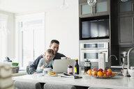 Father and daughter enjoying kitchen breakfast at laptop - HEROF25065