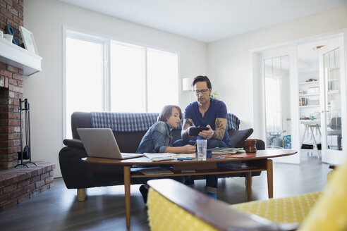 Father helping son with homework in living room - HEROF25074
