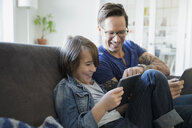Father and son using digital tablets on sofa - HEROF25077