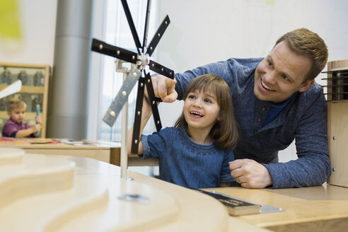 Father daughter playing metal wind turbine science center - HEROF25095