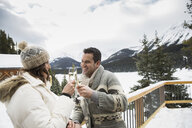 Couple toasting champagne glasses on snowy deck - HEROF25116