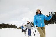 Couples snowshoeing in snowy field - HEROF25119