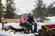 Couple roasting marshmallows at fire pit in snow - HEROF25122