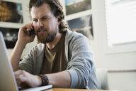 Designer talking on cell phone at laptop - HEROF25158
