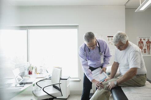 Doctor examining senior mans knee in examination room - HEROF25170