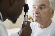 Doctor checking senior mans eyes with otoscope - HEROF25173