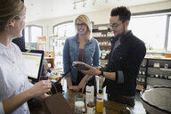 Couple paying with credit card in apothecary shop - HEROF25203