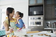 Affectionate mother and daughter baking cookies in kitchen - HEROF25311