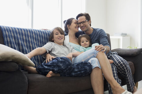 Affectionate family in pajamas relaxing on sofa - HEROF25317