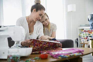 Affectionate mother and daughter measuring sewing fabric - HEROF25320