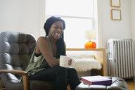 Portrait smiling woman drinking coffee in living room - HEROF25335
