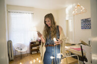 Woman with string lights texting with cell phone - HEROF25347