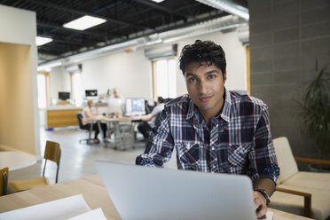 Portrait of businessman working at laptop in office - HEROF25362