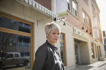 Portrait of smiling blonde woman at urban storefront - HEROF25371