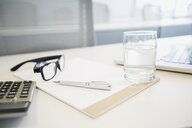 Water glass, notepad, pen, eyeglasses and notepad - HEROF25455