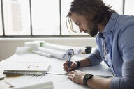 Architect drafting blueprints at table - HEROF25464