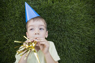 Boy in party hat blowing party horn blower - HEROF25518