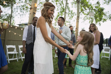 Bride and flower girl dancing backyard wedding reception - HEROF25536