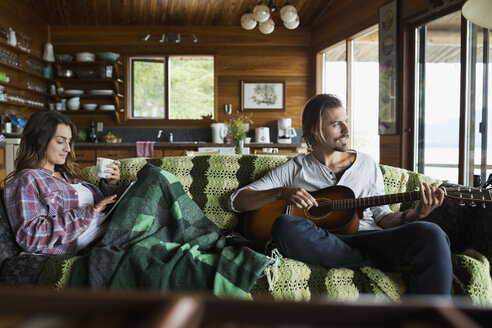 Young couple relaxing playing guitar on cabin sofa - HEROF25680