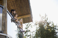 Young friends at cabin balcony railing - HEROF25692