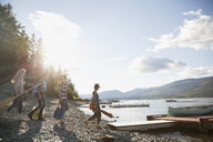 Young friends carrying canoe paddles toward lake dock - HEROF25698