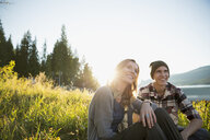 Young couple relaxing in sunny grass - HEROF25710