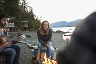 Young friends roasting marshmallows playing guitar lakeside campfire - HEROF25719