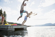 Young men jumping from dock into lake - HEROF25761