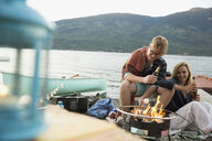 Young couple drinking beer roasting marshmallows lakeside campfire - HEROF25794