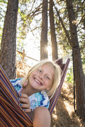 Portrait of happy girl sitting in hammock against trees at forest - CAVF60660