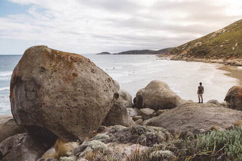Rear view of hiker looking at sea while standing on rock in Wilsons Promontory National Park - CAVF60690