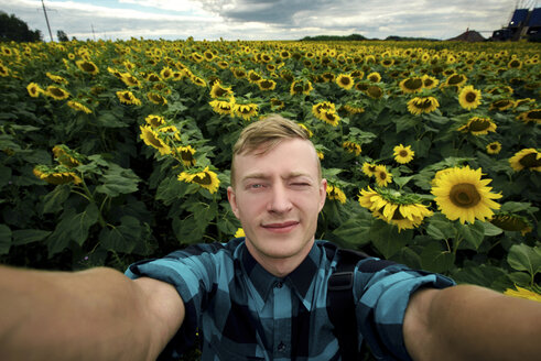 High angle portrait of man winking eye while standing amidst sunflowers growing at farm - CAVF60720
