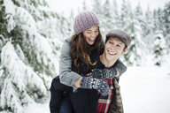 Happy boyfriend piggybacking girlfriend while standing in snow covered forest - CAVF60723