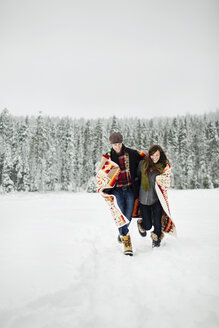Happy couple with blanket running on snow covered field against sky in forest - CAVF60726