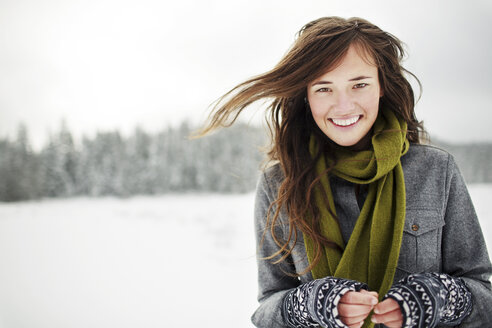 Portrait of smiling woman standing against sky in snow covered forest - CAVF60729