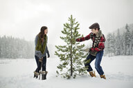 Happy couple standing by pine tree on snow covered field against sky in forest - CAVF60732