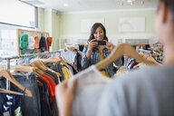 Woman photographing friend holding shirt in clothing shop - HEROF25816