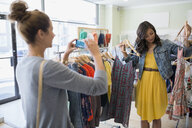 Woman photographing friend holding dress in clothing shop - HEROF25819
