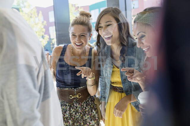 Smiling women window shopping and pointing at storefront - HEROF25825