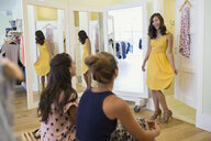 Woman trying on dress for friends clothing shop - HEROF25828