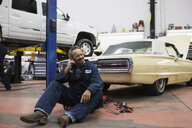Smiling mechanic talking cell phone auto repair shop - HEROF25834
