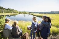 Smiling women with picnic basket at sunny lake - HEROF25885